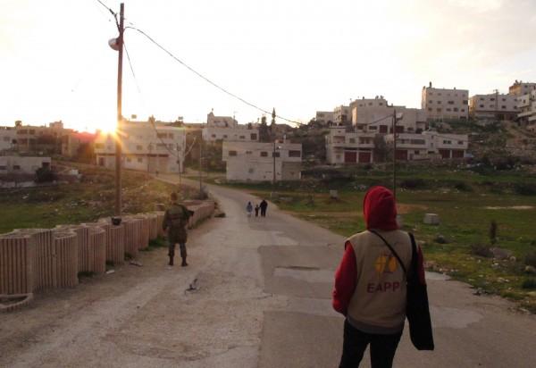 Israeliska bosättare, israelisk soldat och följeslagare på Prayer's Road. Foto: Eric Röst