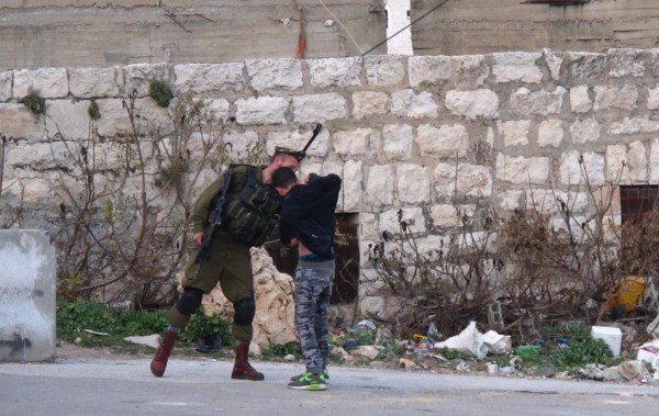 Palestinsk pojke kroppsvisiteras av israelisk soldat. Foto: Eric Röst