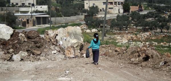 En flicka går på vägen som sedan två dagar är avspärrad. Vägen är den norra infarten till byn Hajja på nordvästra Västbanken. Foto: Malin Andrén