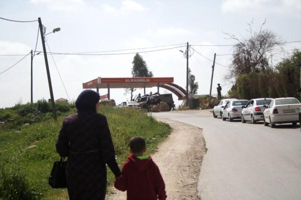 En kvinna och hennes son går mot den temporära vägspärren i Hajja. Längst upp i backen syns ett militärfordon och ett antal soldater. Foto: Malin Andrén