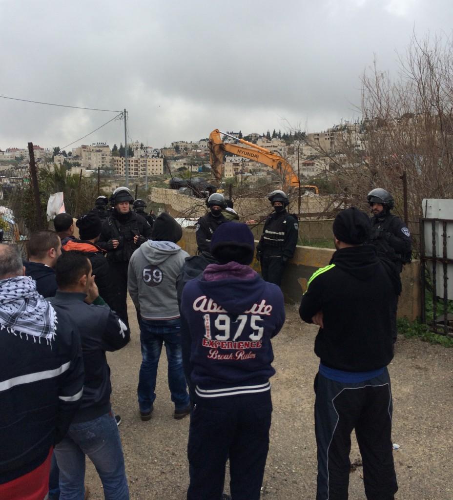 Palestinska män från grannskapet har samlats för att se på när huset i Beit Hanina rivs. Mellan männen och huset står israelisk polis. I bakgrunden syns bulldozern och de delar av huset som fortfarande står upp. Foto: Malin Andrén