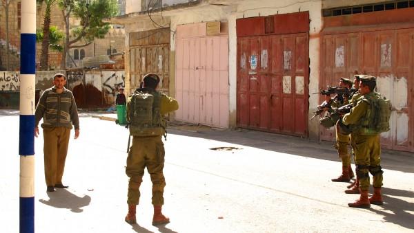 Israeliska soldater siktar sina vapen mot palestinsk man vid vita streckens vägspärr i centrala Hebron. Foto: Mia Haglund