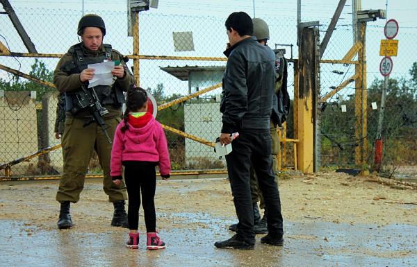 En man och en liten flicka får sina tillstånd kontrollerade av en soldat vid grinden i Deir al-Ghusun norr om Tulkarem. Foto: A Dunne.
