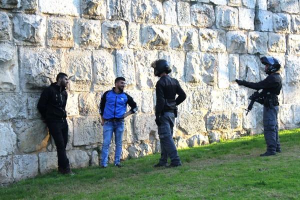 Två unga palestinska män har blivit stoppade, får visa legitimation och blir utfrågade av israelisk polis längs muren till Jerusalems gamla stad. Foto: Alex Dunne