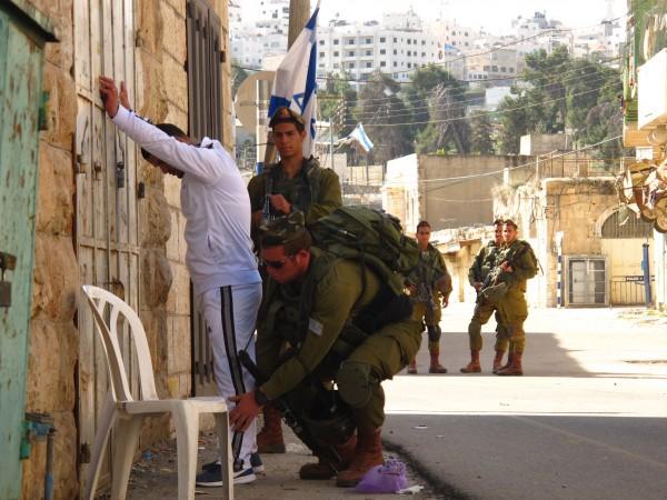Palestinsk man kroppsvisiteras av israeliska soldater i närheten av Ibrahimi moskén. Foto: Mia Haglund
