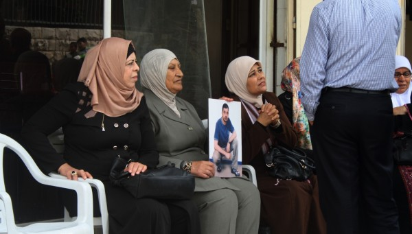 Kvinnor sitter utanför Internationella Rödakorskommitténs kontor i Tulkarem för att delta i den fredliga demonstrationen som hålls en gång i veckan. I handen har en kvinna en bild på en manlig släkting som sitter fängslad i ett israeliskt fängelse. Foto: Malin Andrén.