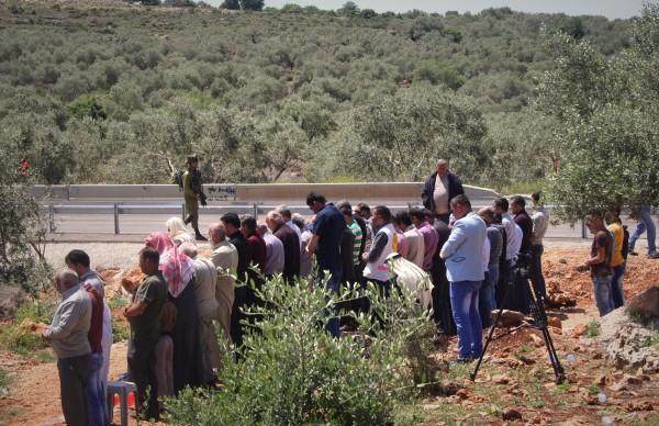 En israelisk soldat patrullerar vägen medan ett femtiotal män från Deir Istiya ber sin fredagsbön. Foto: EAPPI/M Andrén