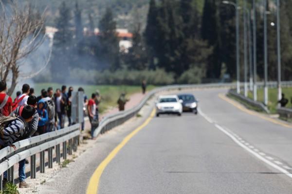 Palestinska skolelever på väg hem från skolan. En pojke ser över räcket för att se fyra israeliska soldater kanta vägen längre ner. Foto: Petter Lämås.