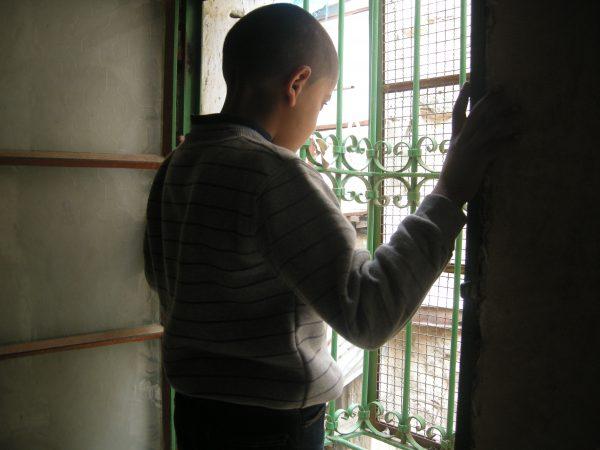 Anaas Eqneibi, 8 år, betraktar grannlägenheten som är en del av den illegala israeliska bosättningen Avraham Avinu. Foto: Per Anders Skytt