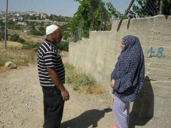 Abdel Karim Jabari med sin dotter Ayatt framför den mur de byggt runt sitt hem i ett försök att hålla bosättare borta. Foto: Per Anders Skytt