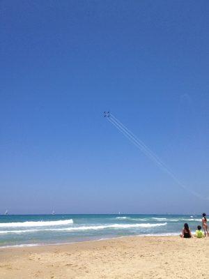 Går det att blunda från ockupationen? Också på stranden i Tel Aviv gör sig militären påmind. Badgäster betraktar en imponerande flyguppvisning av det israeliska flygvapnet under Israels självständighetsdag. Foto: Josefin Hjärpe Lämås