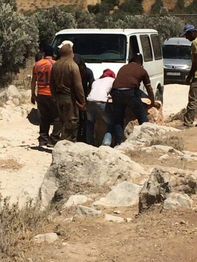 """""""Vi ger oss aldrig"""". Unga män flyttar stenar som blockerar vägen till Yatta. Foto: Maria Kileby"""