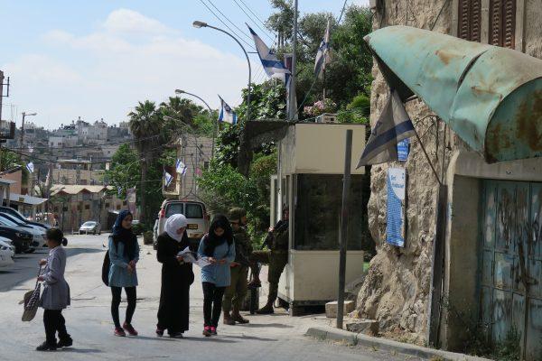 Några flickor passerar genom en militärkontroll på väg hem från skolan i Hebron. Foto: Erika Karlsson
