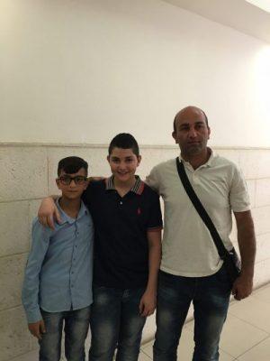Shadi poserar för en bild med sin pappa och kompis. De får ses i tio minuter efter förhandlingarna i domstolen innan Shadi och Ahmed transporteras tillbaka. Foto: Johanna Svanelind
