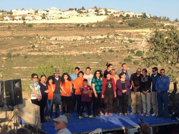 Stora delar av familjen Nassar samlad på scenen under firandet av att familjen ägt marken i 100 år den 12 maj 2016, i bakgrunden den olagliga bosättningen Neve Daniel. Bild: Christer Wik