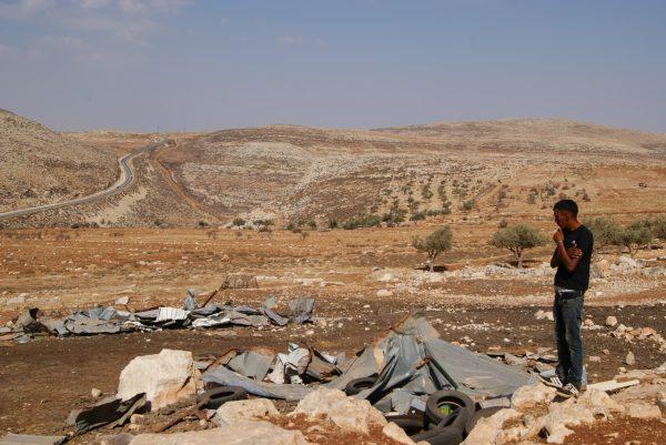 Bassem visar oss deras hem vid bergssluttningen som förra året blev rivna. Han pekar även på ett ställe längre ner, på andra sidan vägen där getterna blev attackerade. Foto: Zeinab