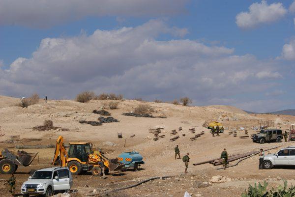 Grävskopor och militär under pågående husrivning