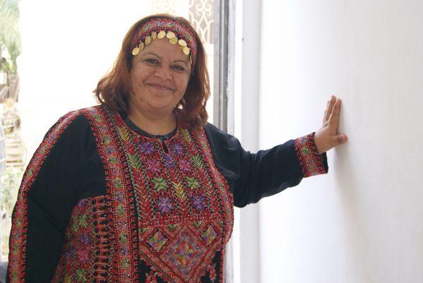 Nihaya tar på sig en av klänningarna hon har skapat och visar upp den för oss. Foto: Zeinab El-Saneh