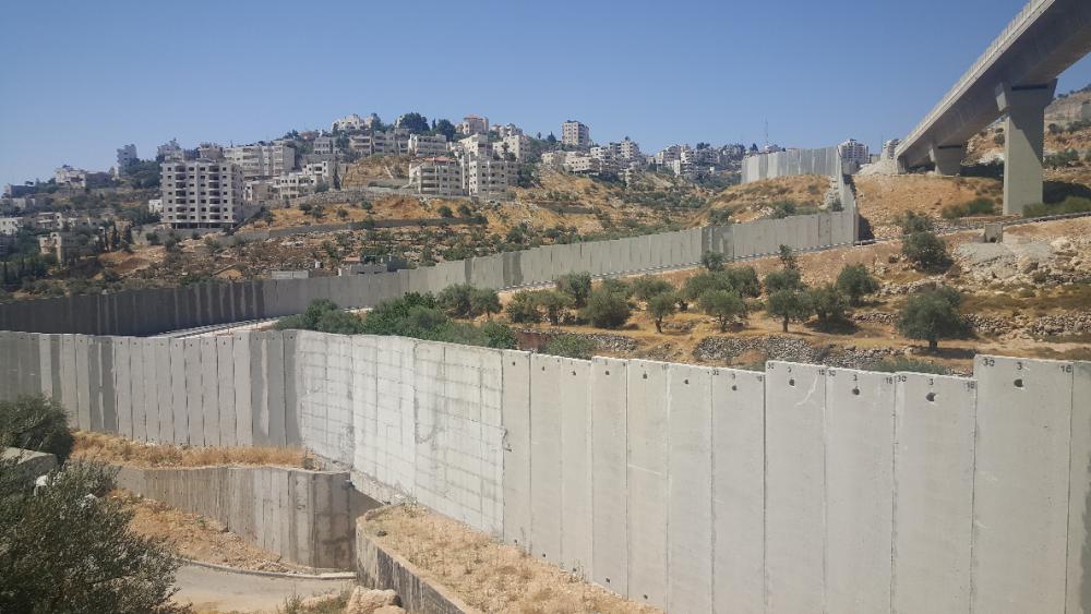 Muren som delar Cremisandalen från Palestina. Nere till vänster syns den port som öppnas vid olivskörden. Foto: S. Sjöblom